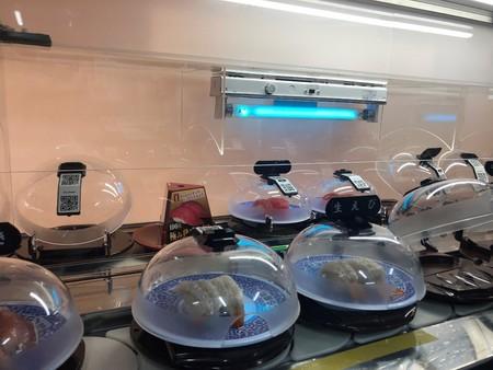 寿司カバーを紫外線殺菌灯に照射する様子